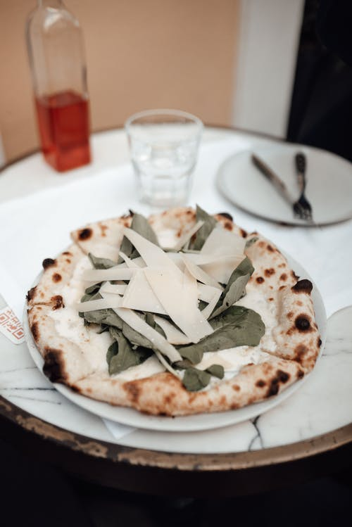 From above of delicious pizza with Parmesan cheese and spinach served on plate on round marble table on restaurant terrace
