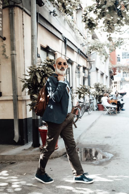 Side view of fashionable bearded senior ethnic male tourist in stylish clothes and sunglasses walking in city old district during vacation on sunny day