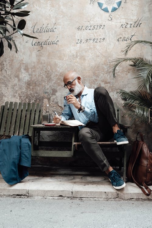 Full body of concentrated senior bearded ethnic male author in stylish clothes and eyeglasses drinking coffee and writing new article in notebook while relaxing in outdoor cafe
