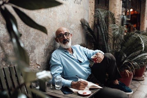 Positive senior ethnic male freelancer with white beard in trendy outfit drinking coffee and taking notes in organizer while working remotely in cafe