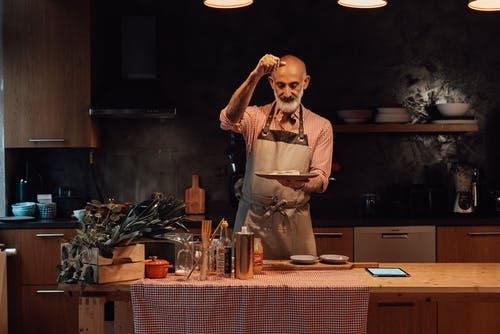 Positive bearded senior ethnic male chef in casual clothes and apron salting dish while standing at table in modern kitchen