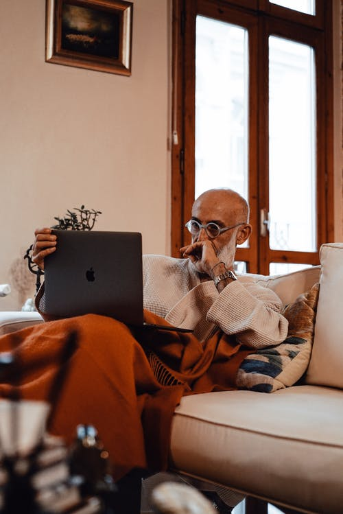 Concentrated elderly bearded ethnic male freelancer in robe and eyeglasses sitting on comfortable sofa and working remotely on laptop at home