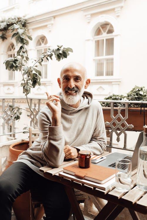 Elderly ethnic man smiling at camera while working remotely on laptop on balcony