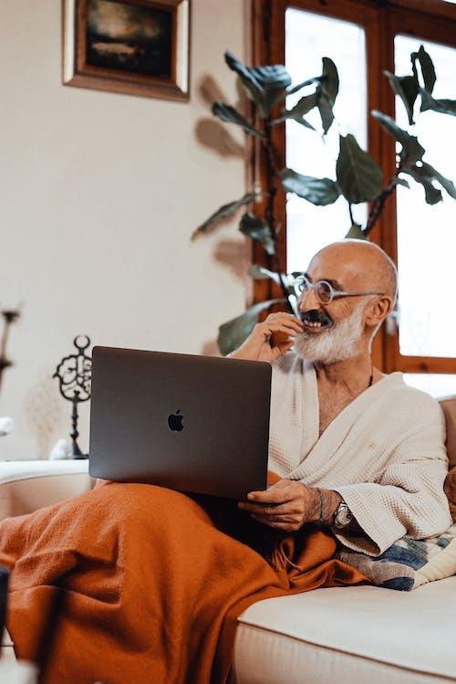 Pria Berkemeja Putih Menggunakan Macbook