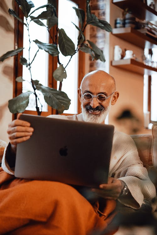 Happy bearded senior ethnic male in robe and eyeglasses resting on couch at home and smiling while having video call on laptop