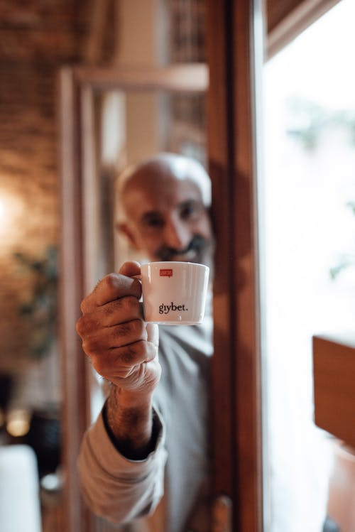 Happy mature bearded ethnic male in casual clothes smiling while demonstrating cup of aromatic espresso in cafe