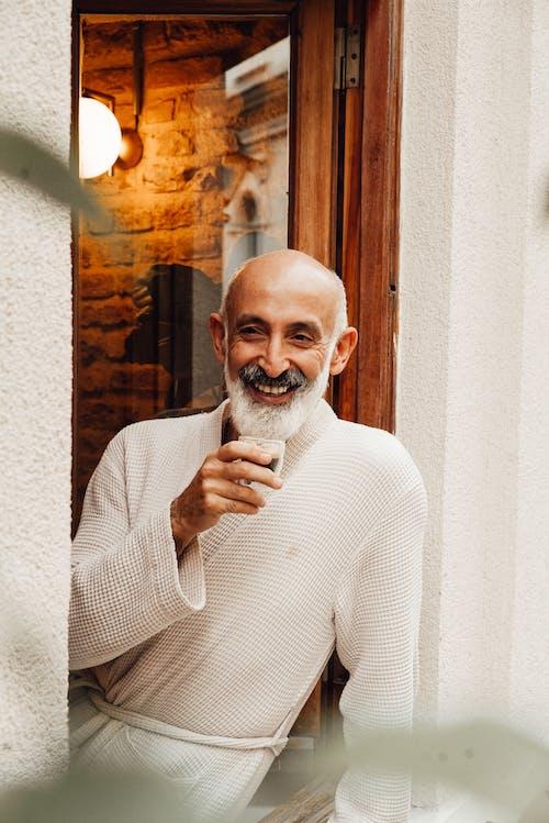 Happy elderly ethic man drinking coffee on balcony