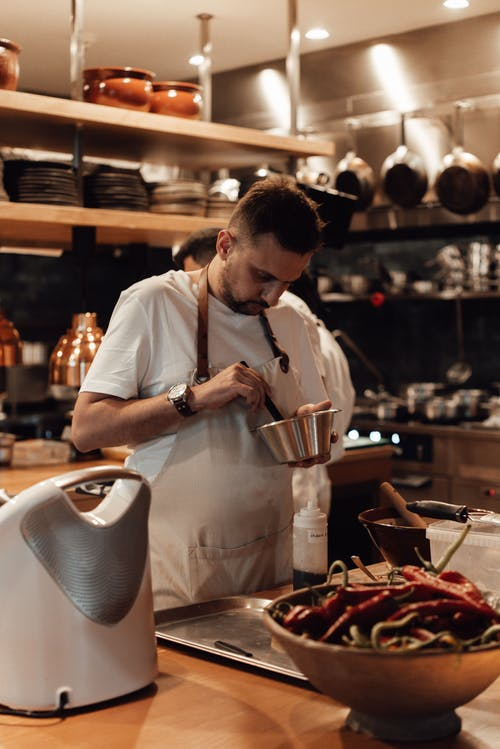 Serious man cooking food at table in restaurant kitchen