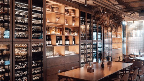 Wall with shelves with collection of assorted wine in modern restaurant with wooden furniture and creative decor
