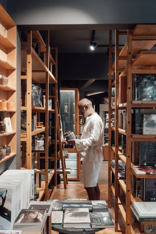Side view of thoughtful ethnic man in casual clothes standing among wooden shelves and choosing books in store