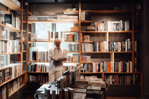 Focused senior ethnic man in casual clothes standing and reading book against bookshelves in store in daytime