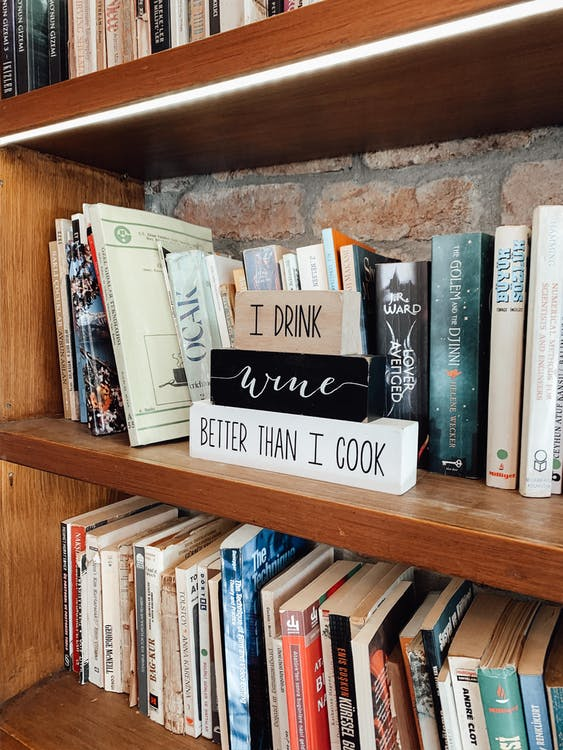 Collection of assorted books and decorative wooden elements with inscription I drink vine better than i cook placed on shelves in bookstore in daytime