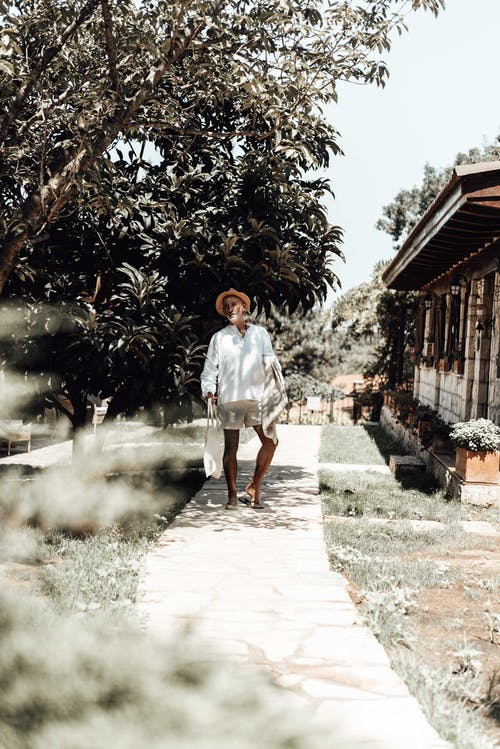 Full body of calm ethnic man in stylish clothes and hat walking along narrow roadway placed among green trees and building in resort area in sunny day