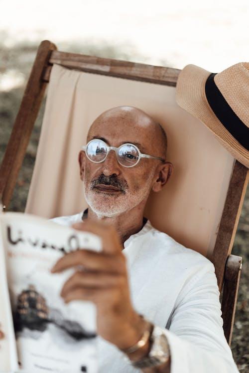 茶色のfedora帽子をかぶった白いクルーネックシャツの男