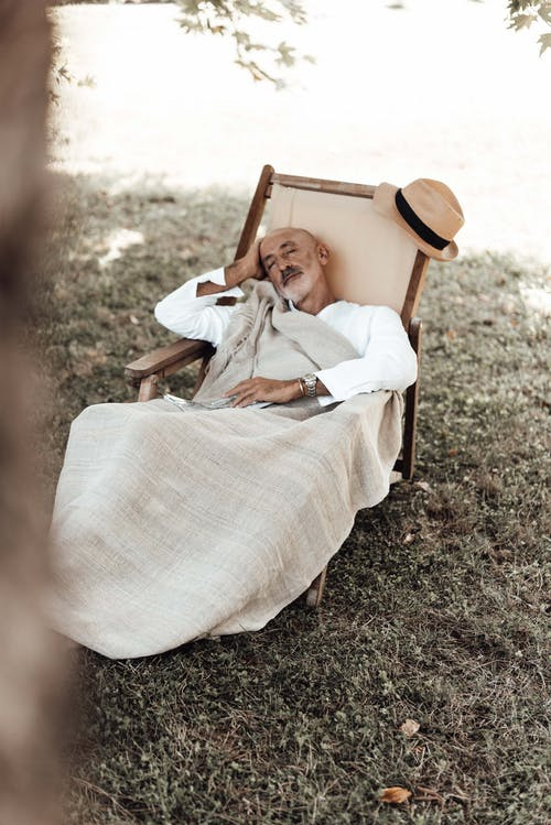 Calm aged ethnic man in casual clothes lying with closed eyes on comfortable chair in nature in sunny day