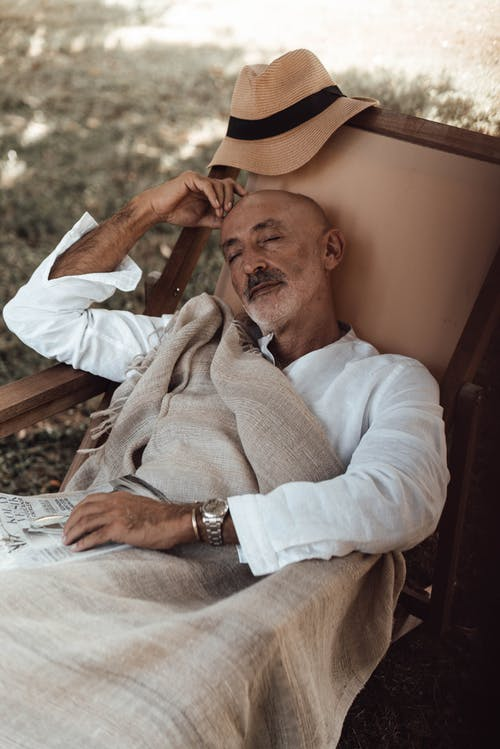 From above of tranquil ethnic man in stylish clothes lying on chair and sleeping in nature in daytime