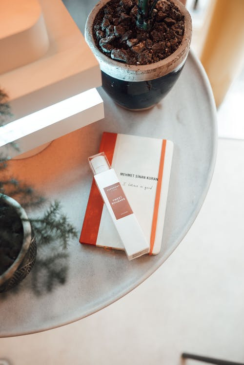 From above of bottle of perfume and notebook placed on round table near potted plants in modern apartment