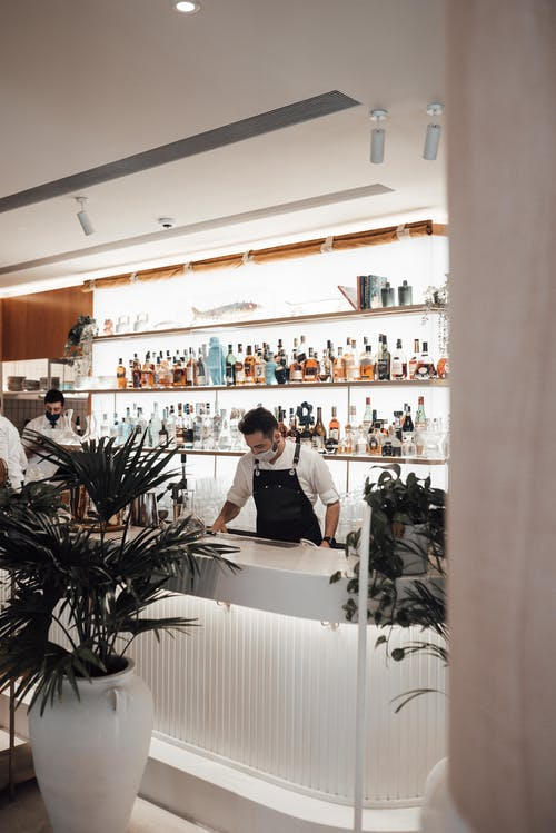 Unrecognizable male bartenders in aprons and face masks standing at counter near shelves with assorted alcohol drinks during work in modern bar