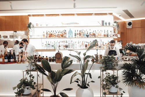 Unrecognizable male bartenders standing at counter near shelves with various drinks in restaurant