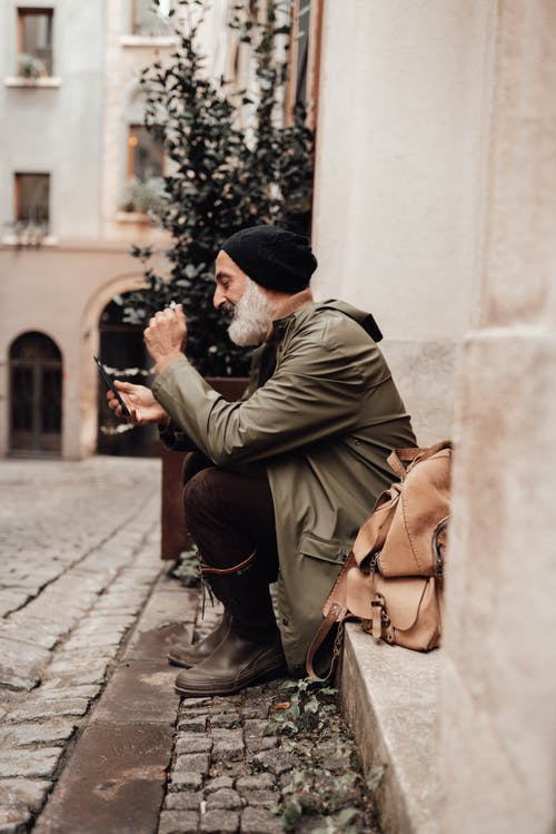 Мужчина в коричневом пальто и черной вязаной шапке держит смартфон