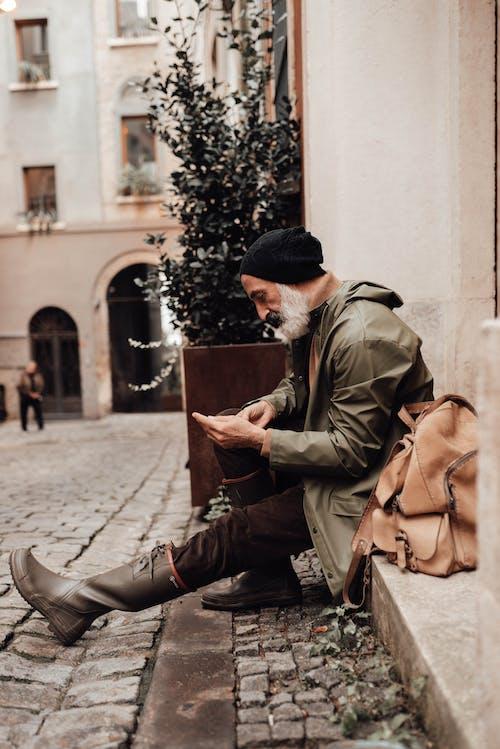 Unshaven Hispanic traveler chatting on smartphone in city