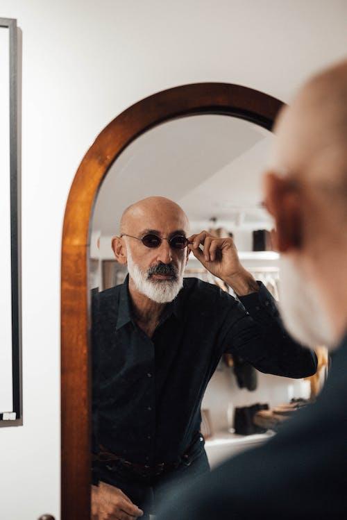 Confident elderly ethnic man adjusting sunglasses near mirror in store