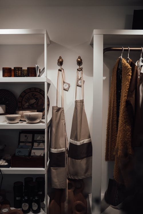 Collection of trendy clothes and assorted pottery in modern boutique