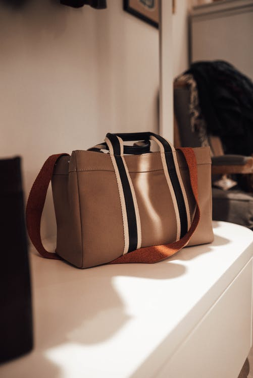 Stylish beige shopper bag with long strap placed on shelf in modern fashion boutique