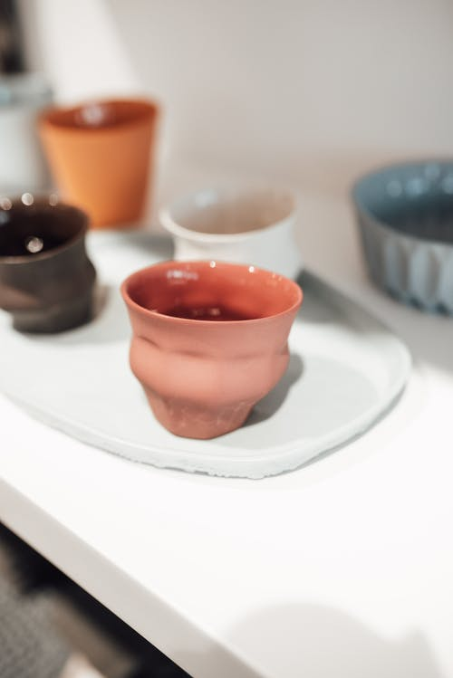 Ceramic cups placed on white shelf