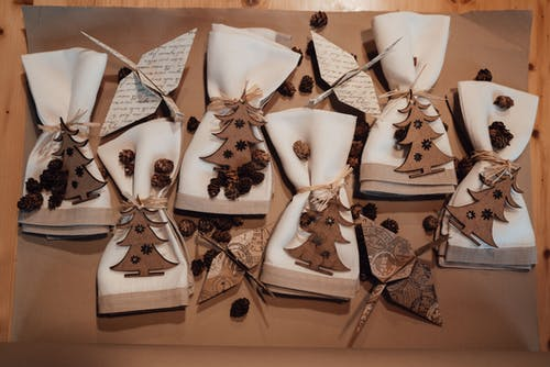 From above of carton on table with napkins covered in ropes decorated with bumps near small wooden Christmas trees and near origami cranes from paper in bright room
