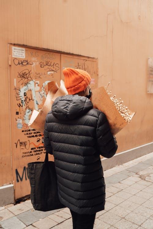 Femme En Veste Bulle Noire Et Bonnet En Tricot Rose Couvrant Le Visage Avec Les Mains