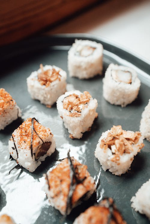 Ceramic plate with various tasty rolls with rice and seasoning with seaweed in bright restaurant on table