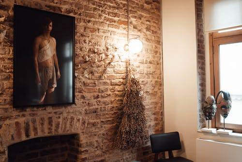 Interior of light cafe with brick wall decorated with picture of man near lamp and hanging garland with dry herbs near chair and window with African masks on windowsill