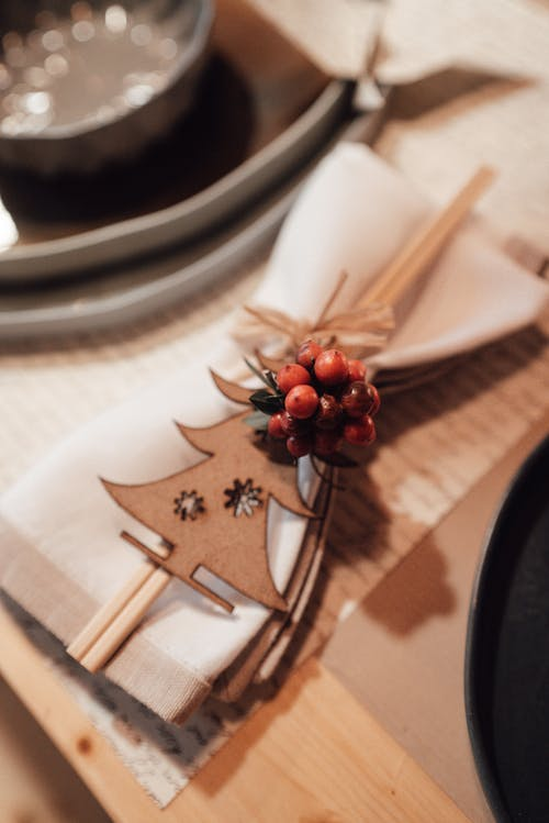 Table with napkin with decorative elements and chopsticks near utensil