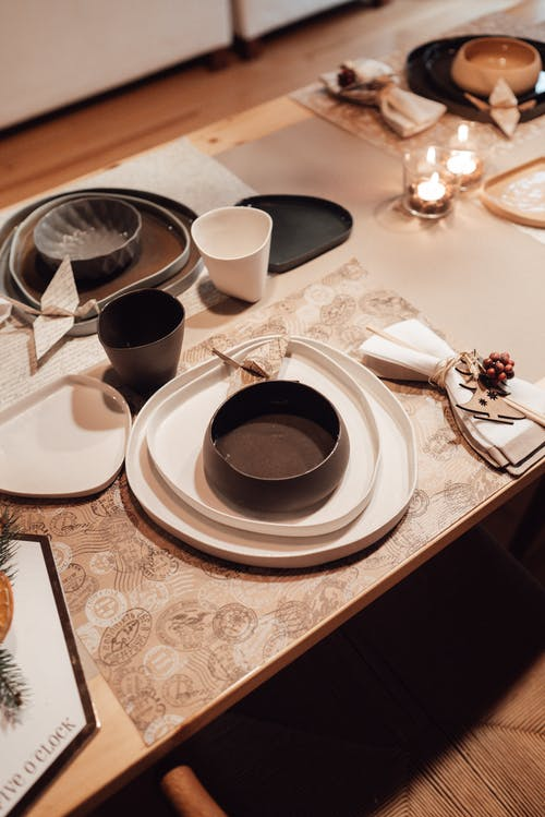 High angle of table with plates and bowls near cups and paper origami cranes near napkins with small wooden Christmas tree and candles in light house