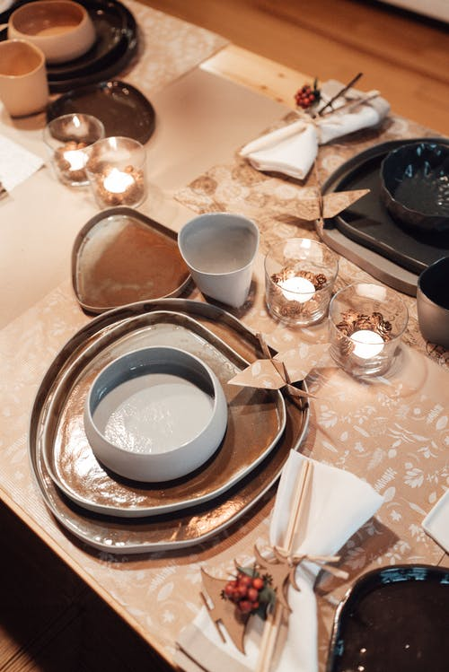 From above of various dishware placed on served table with burning candles and folded napkins near traditional orizuru at home