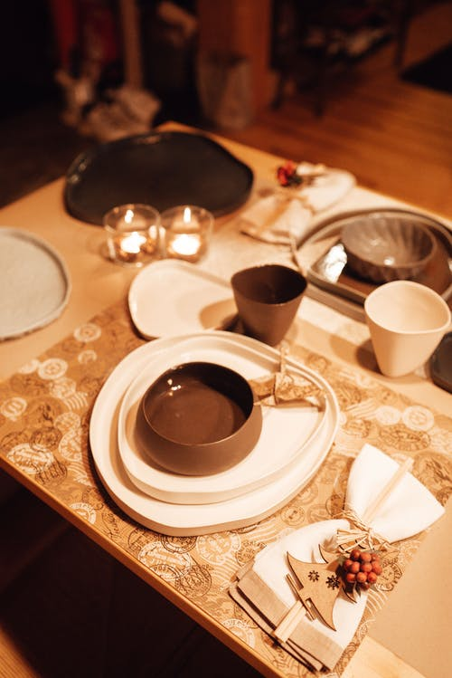 From above of dinnerware with plates and cups served on table with burning candles in modern dining room at home