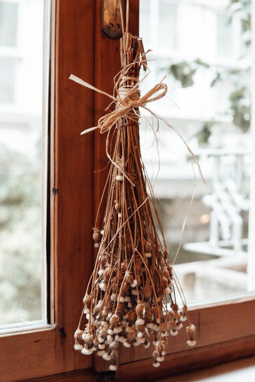 Bouquet of dried flowers tied with rope hanging on widow with wooden frame in room on blurred background at home