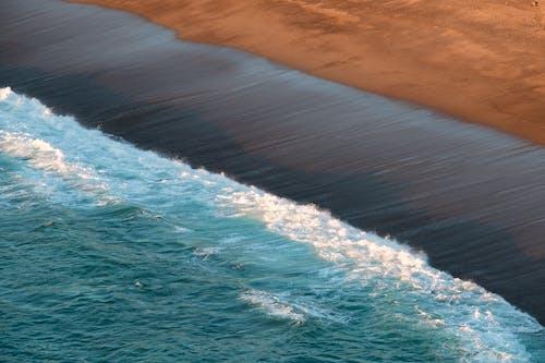 Foaming sea rolling on wet sandy beach