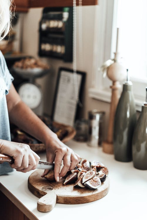 Unrecognizable female cook with knife cutting heap of figs on wooden cutting board while standing at kitchen counter on blurred background
