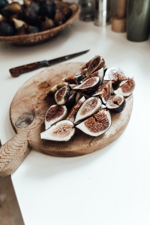 Heap of cut ripe figs on wooden cutting board placed on white counter with knife and bowl of fruits in kitchen
