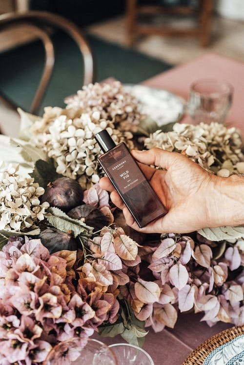 Person showing fragrant perfume against blooming flowers