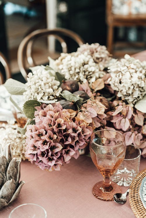 High angle of bouquet of blooming flowers placed on table near glassware for reception