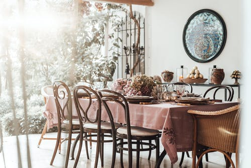 Interior of dining room with table served with dishware and glassware placed near decorative flowers for festive event
