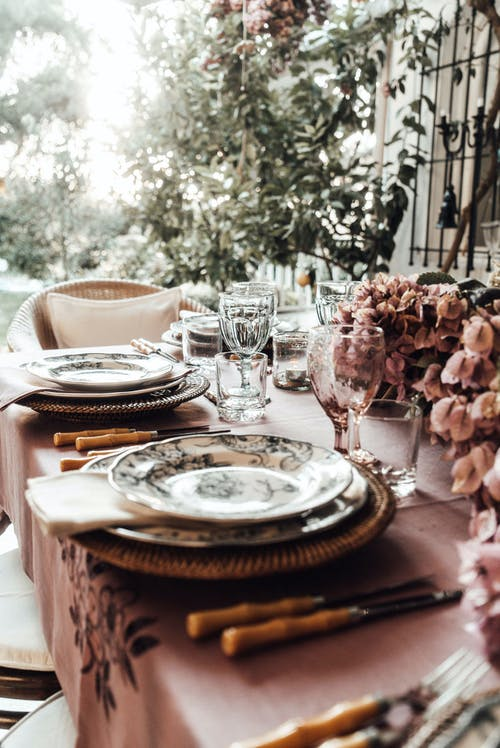 Banquet table with dishware and wineglasses near bunches of flowers