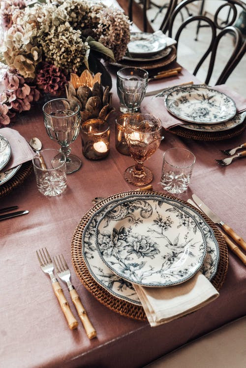 High angle of plates with cutlery placed near glassware on table decorated with burning candle and blooming flowers