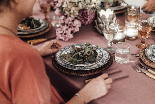 High angle side view of crop female with portion of salad sitting at festive table decorated with blooming flower and burning candles