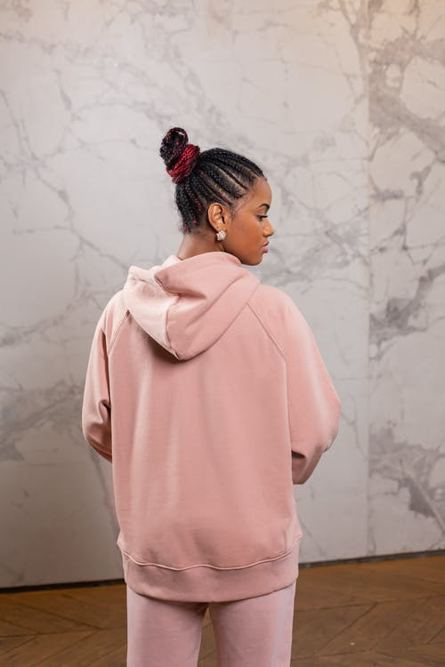 Back view of young African American female millennial with traditional braids in stylish pink hoodie standing in light room and looking away