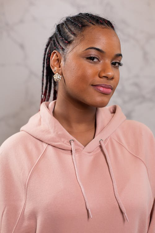 Self assured young black female model with Afro braids and perfect skin in stylish pink hoodie smiling while looking at camera against gray background