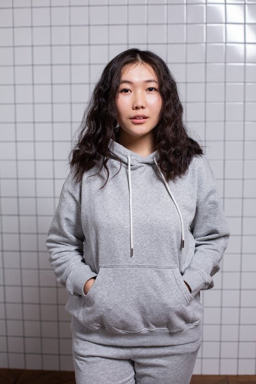 Positive Asian female teenager with dark wavy hair standing with hands in hoodie pocket and looking at camera in light room with tiled wall